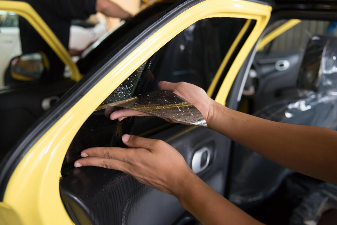 Picture of a yellow car door with a person applying tint to the window